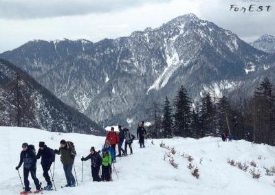 Escursionisti con le ciaspole e panorama sulla Cima del Cacciatore e Monte Santo di Lussari